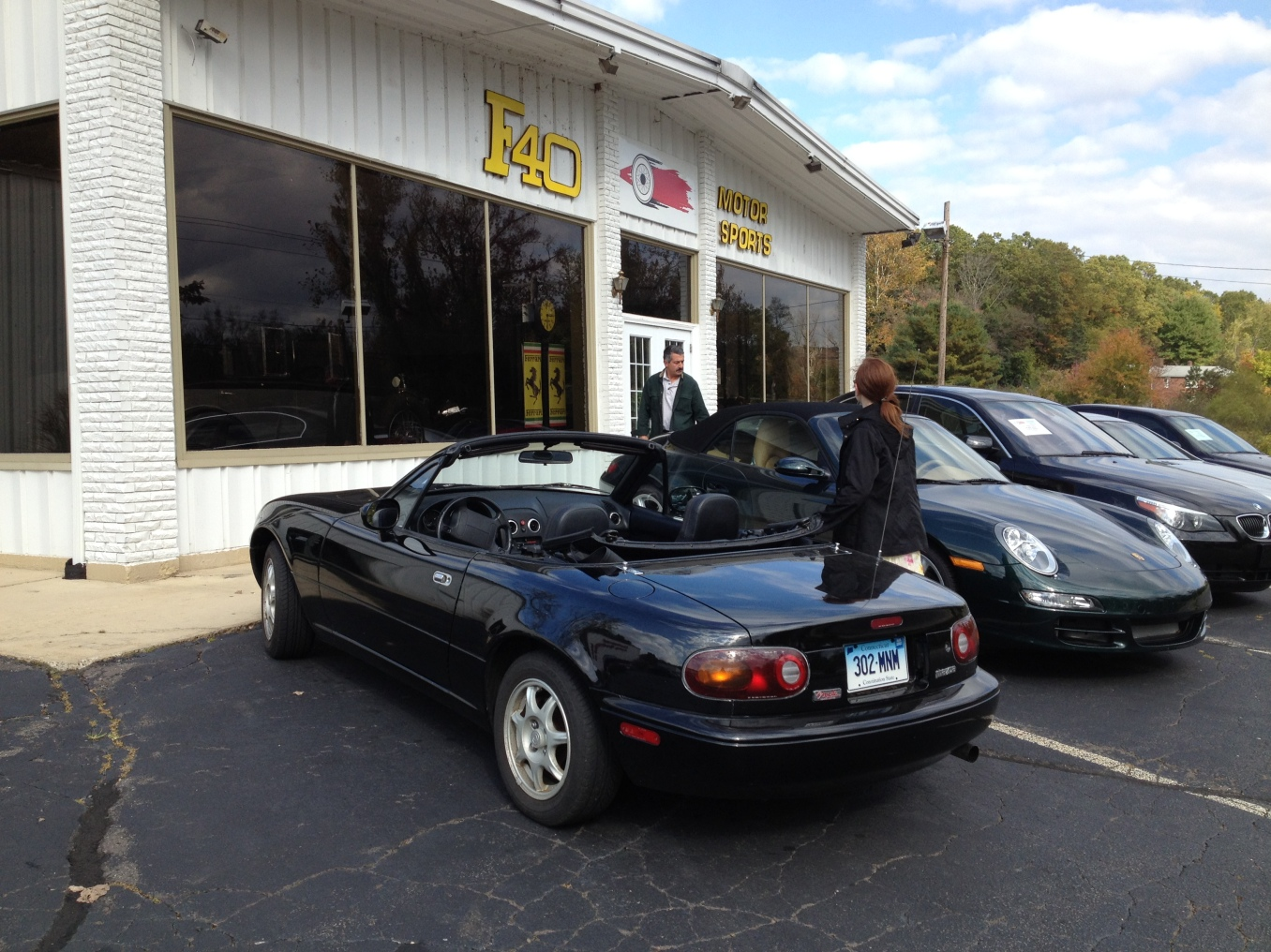 Our first Miata, the 1994 A-Package, pictured ca. 2016 with my daughter outside Wayne Carini's F40 Motorsports in Portland, CT